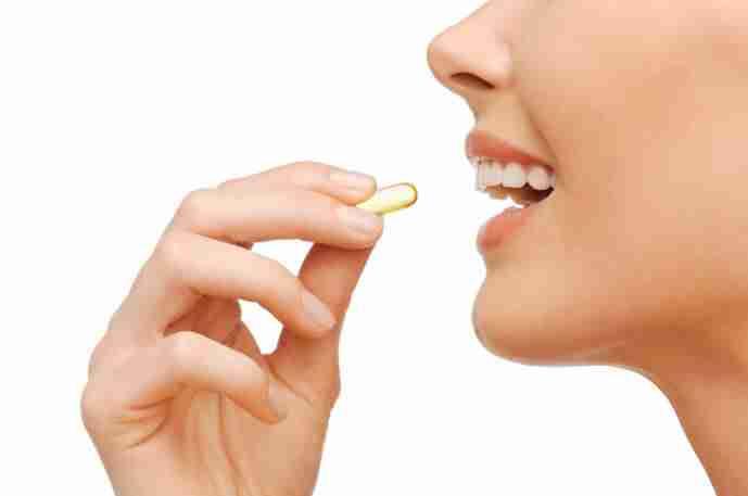 mulher tomando cápsulas